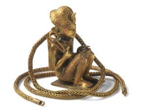 Figurine prosternée et chaîne en or représentant un roi accroupi 18e dynastie, règne de Toutânkhamon, 1336 - 1326 av. J.-C. Or Hauteur (sculpture) : 5.4 cm Longueur (de la chaine) : 54 cm Diamètre (de la chaine) : 0,3 cm Louxor, Vallée des Rois, KV62, chambre du trésor